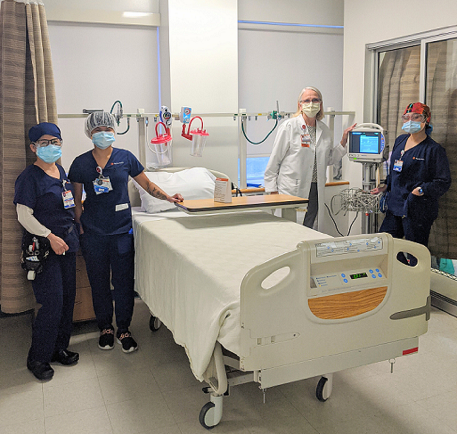Four nurses stand around a patient bed and new DASH monitors