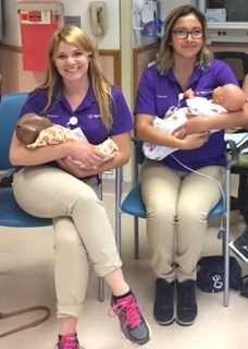 Two female volunteers hold tiny newborn babies