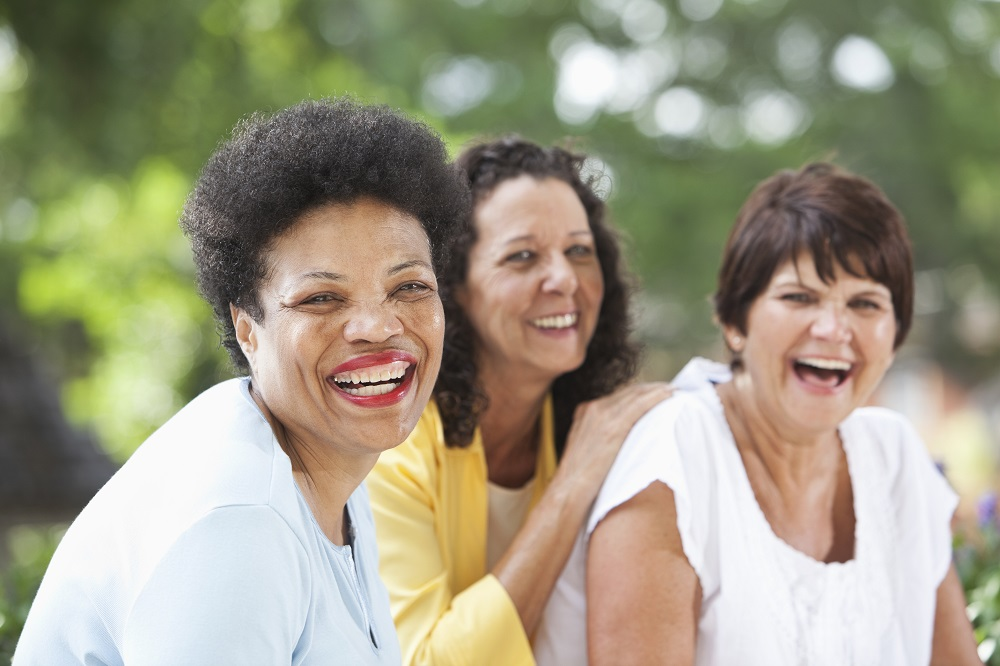Three women laugh together while sitting outside